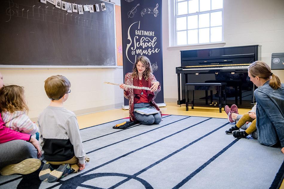 teacher Sarah Greene demonstrating a flute to a Mini Maestro class.