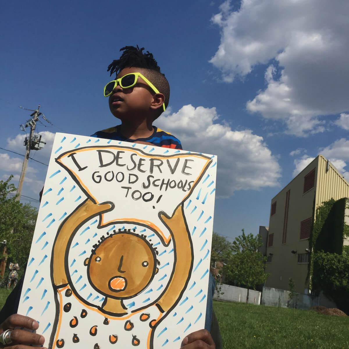 A young child holding a I deserve good schools too sign.