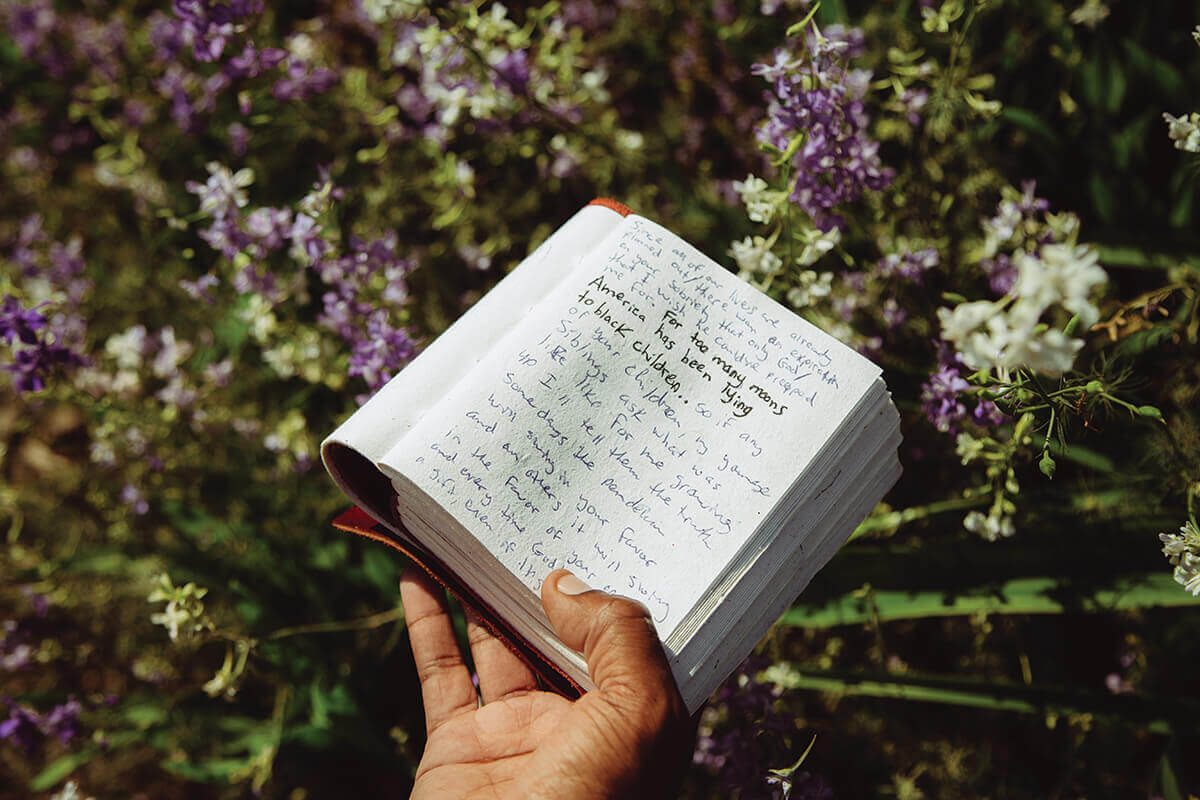 Fidel holds his writing journal at Cylburn Arboretum. His new book, the antiracist, is due out august 11.