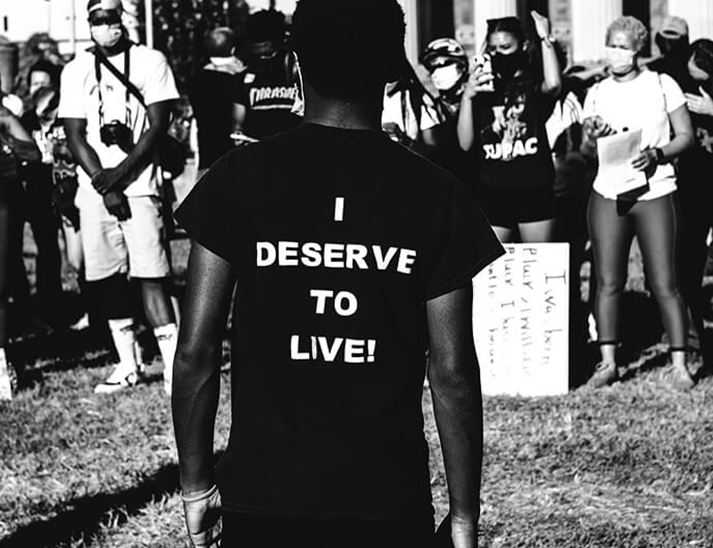 A young man facing towards a crowd in front of Baltimore City Hall with the words I deserve to live on the back of his shirt.