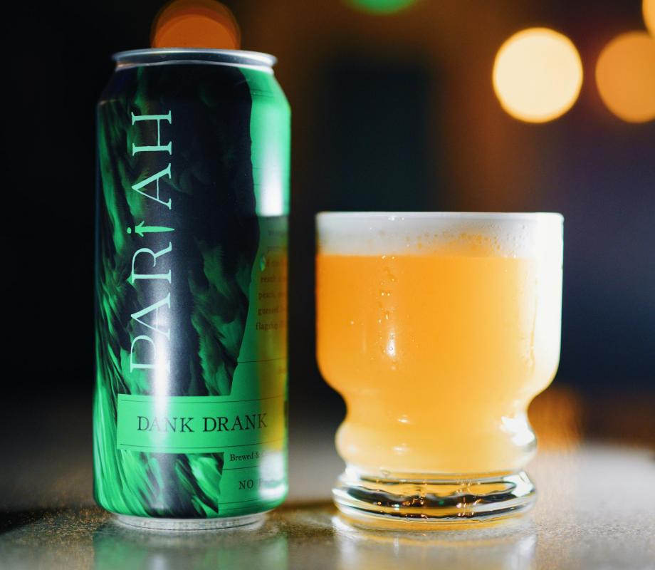 Pariah Brewing Co. beer can next to glass of beer